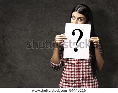 portrait of young woman showing a interrogation symbol against a grunge background