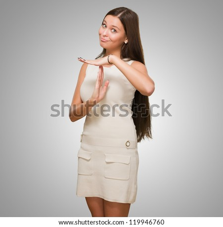 Portrait Of Young Woman Showing Time Out Signal against a grey background