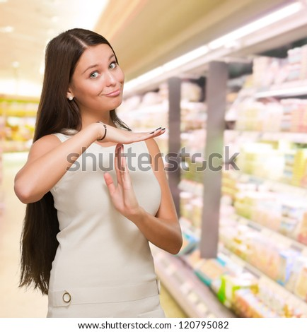 Portrait Of Young Woman Showing Time Out Signal at a supermarket