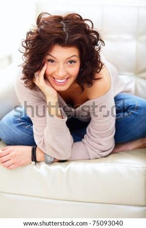 Portrait of young woman sitting at sofa at home, looking at camera, smiling.