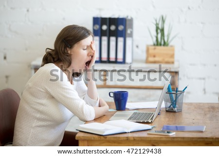 Portrait of young woman sitting at table in front of laptop, sleepy, tired, overworked, lazy to work. Attractive business woman yawning in home office relaxing or bored after work on laptop computer #472129438