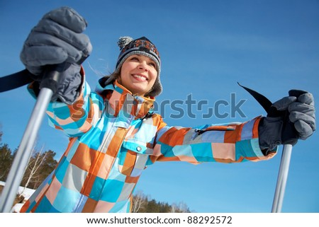 Portrait of young woman skier on blue sky background