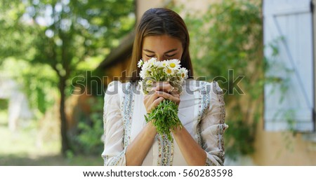 Portrait of young woman smells a heap of daisies collected by herself in her own countryside house's green flower full garden. Concept good memories, bride, marriage, happiness