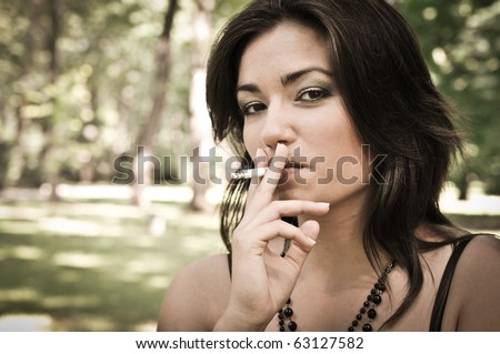 Portrait of young woman smoking cigarette outdoors in sunny green park