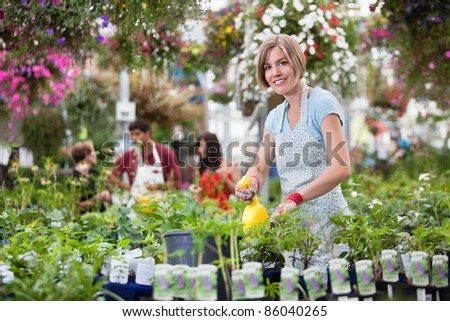 Portrait of young woman spraying plants
