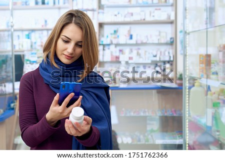 Portrait of young woman standing in drugstore and taking photo of medicine using smartphone. Female customer holding white pills bottle and phone, looking for medicine at drugstore.