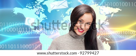 Portrait of young woman standing in front of big world map and different icons flying overhead