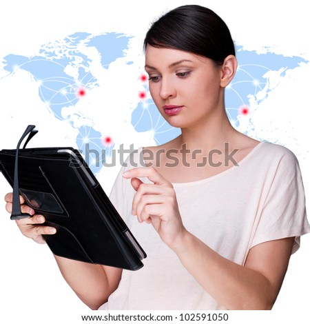 Portrait of young woman standing in front of big world map and looking at her tablet computer.