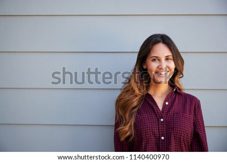 Portrait Of Young Woman Standing Outside Grey Clapboard House #1140400970