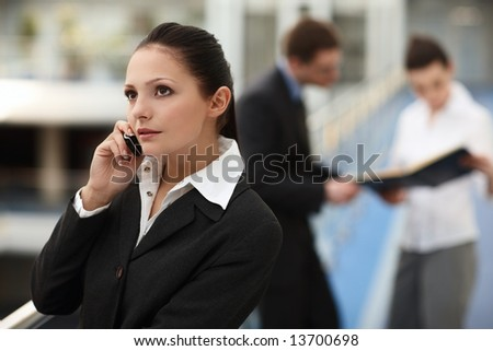 Portrait of young woman standing talking on the phone in modern business office building corridor