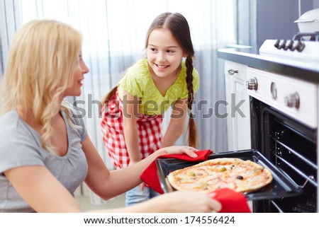 Portrait of young woman taking pizza out of oven with her daughter standing near by