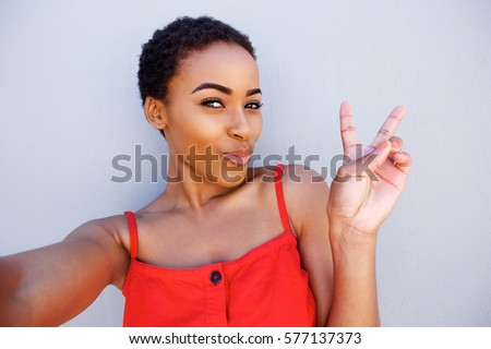 Portrait of young woman taking selfie with peace hand sign