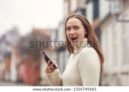 portrait of young woman talking on mobile phone outside looking in camera with open mouth  #1324749683