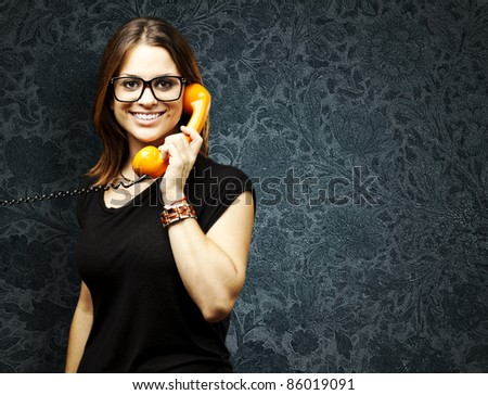 portrait of young woman talking using a vintage telephone against a vintage background