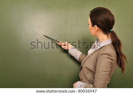 Portrait of young woman teacher standing near blackboard and explaining something pointing at copyspace