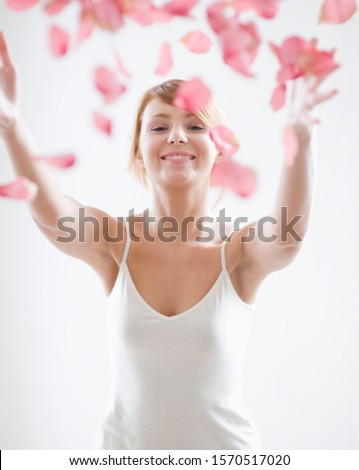 Portrait of young woman throwing pink rose petals, studio shot