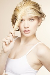 Portrait of young woman twisting blonde hair in studio