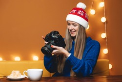 Portrait of young woman wear red Christmas hat indoors. Girl takes photo on professional digital camera dslr, lady is photographer