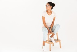 Portrait of young woman wearing eyeglasses sitting on chair and looking aside on copyspace with smile isolated over white background