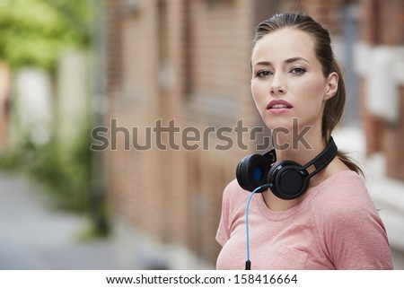 Portrait of young woman wearing headphones outdoors