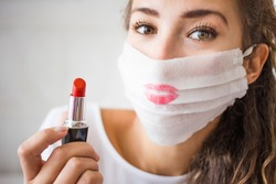 portrait of young woman wearing medical face mask during coronavirus. Make up problem and epidemy. Red lipstick on the protection mask.