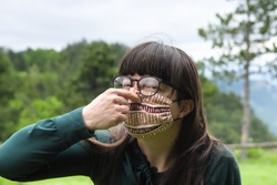 Portrait of Young Woman Wearing Protective mask and holding her Nose as sign of bad air under the mask. Wearing  Protective hygienic face medical mask to prevent flu infection, 2019-nCoV, Coronavirus
