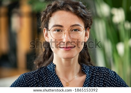 Portrait of young woman wearing spectacles and looking at camera. Close up face of happy girl with glasses smiling at work. Confident and satisfied businesswoman wearing eyeglasses in office.