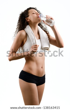 Portrait of young woman wearing sport clothes and drinking water on white background