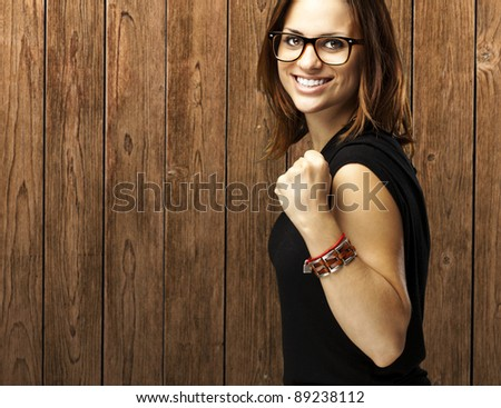 portrait of young woman win gesture against a wooden wall