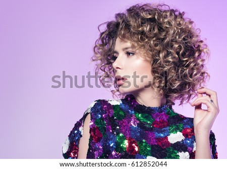 Portrait of young woman with beautiful curly hair. Neutral purple background with free space