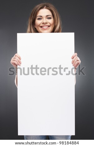 Portrait of young woman with blank white board on gray isolated