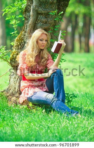 portrait of young woman with book outdoor