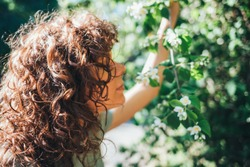 Portrait of young woman with curly hair enjoying scent of blooming tree flowers in garden on sunny summer day.
