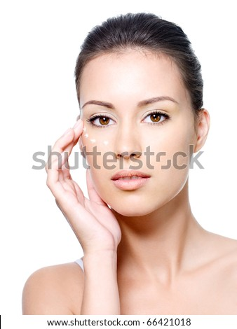 Portrait of young woman with fresh clean face with points of cream under the eye