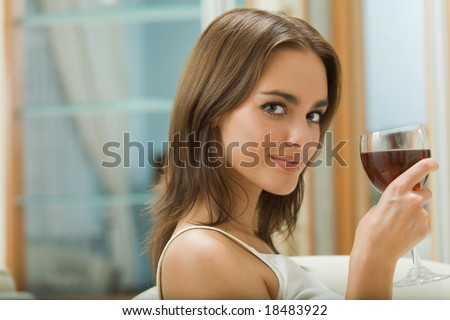 Portrait of young woman with glass of red wine at home
