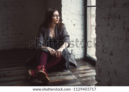 Portrait of young woman with glasses with good skin and hairs sitting on a floor in loft design interior near the window in a autumn coat and red leather shoes  #1129403717