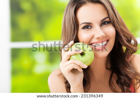 Portrait of young woman with green apple, outdoors, with copyspace