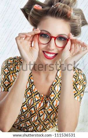 Portrait of young woman with hair curlers wearing red vintage eyeglasses