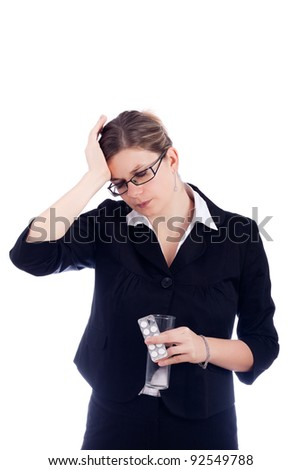 Portrait of young woman with headache, holding glass with water and painkillers. Isolated on white background.