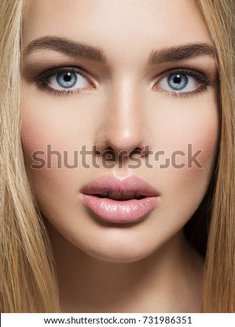 Portrait of  Young Woman with healthy skin of a face. Attractive female with long light straight  hairs and brown make-up.  Pretty gorgeous girl with blue eyes -  posing at studio.