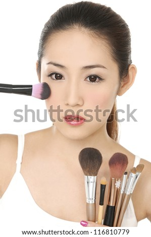 Portrait of young woman with make-up brushes near attractive face.