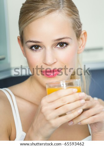 Portrait of young woman with orange juice, indoors
