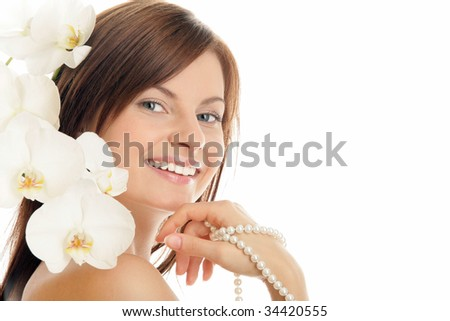 Portrait of young woman with pearl necklace and orchid isolated on white background