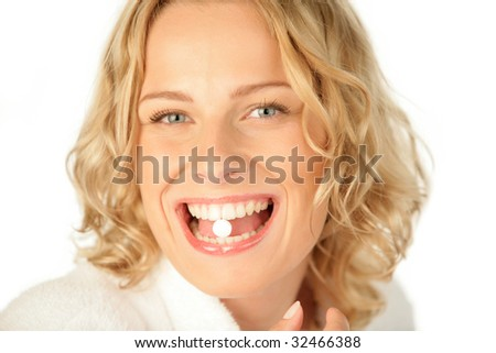 Portrait of young woman with pill in her mouth isolated on white background - stock photo