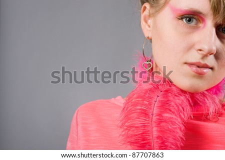 Portrait of young woman with pink plume over gray background. Woman with pink make-up.