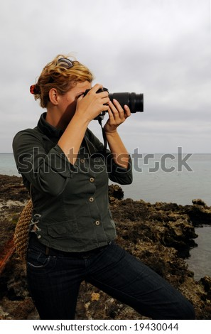 Portrait of young woman with professional dslr camera taking pictures outdoors