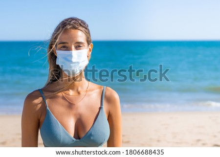 Portrait of young woman with protective mask enjoying on the seaside during the COVID-19.