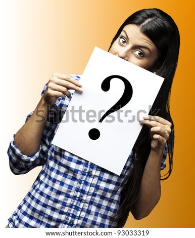 portrait of young woman with question paper on yellow background - stock photo