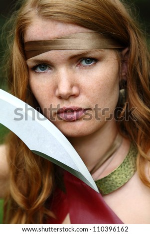 portrait of young woman with sword at forest