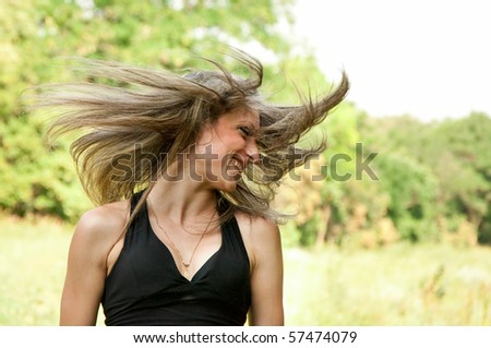 Portrait of young woman with wind blowing hair in the park